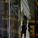 Woman standing in shadows, talking on cel phone in shopping arcade, London, UK